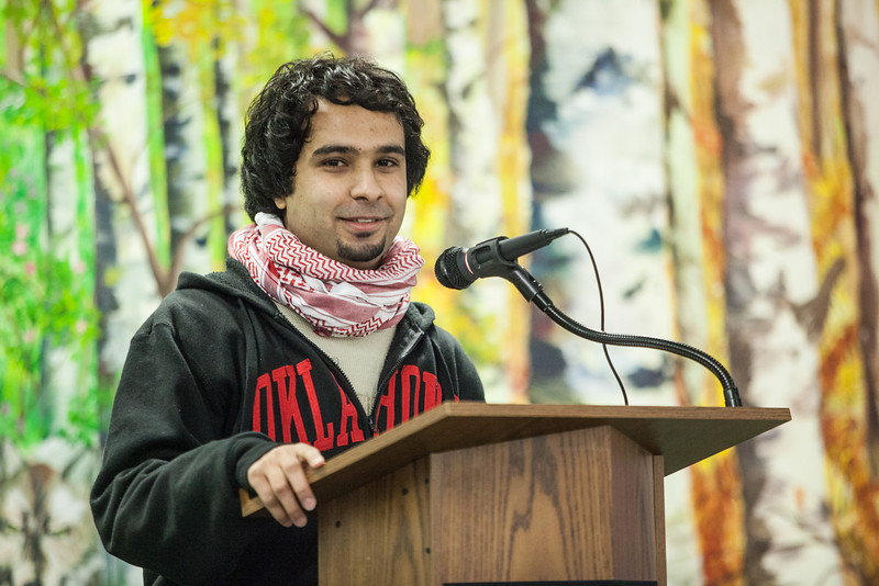 """Fahad Alshamman of Saudi Arabia informs a handful of students, faculty, and community members about his country during a flag dedication ceremony at the Wood Center.  <div class=""""ss-paypal-button"""">Filename: LIF-12-3655-55.jpg</div><div class=""""ss-paypal-button-end"""" style=""""""""></div>"""