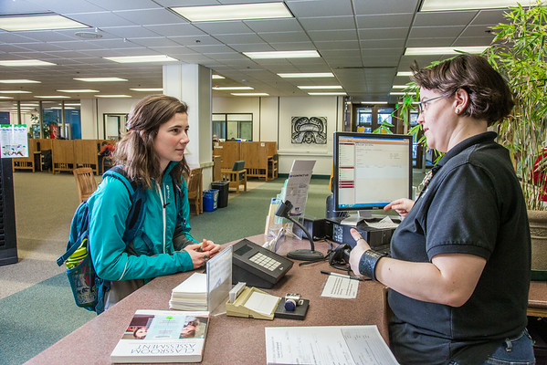 """Sarah King, a junior majoring in elementary education, asks a question at the circulation desk in the Rasmuson Library.  <div class=""""ss-paypal-button"""">Filename: LIF-14-4045-161.jpg</div><div class=""""ss-paypal-button-end""""></div>"""