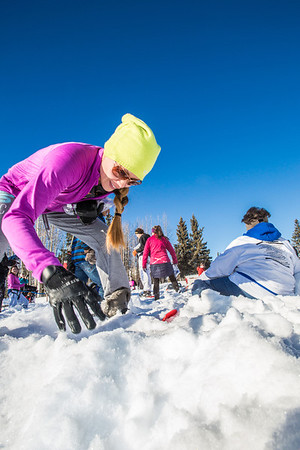 Participants in the second annual Troth Yeddha' Snowshoe Scramble dig for prizes buried in the snow after the race Saturday, March 1 by the Reichardt Building. The event hopes to build awarness for a proposed park to help celebrate Alaska's Native culture.  Filename: LIF-14-4079-114.jpg