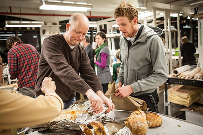 Ceramics professor Jim Brashear prepares another turkey, which was baked in a kiln while student Ian Wilkinson takes out homemade bread during the annual Thanksgiving gathering at the ceramics department.  Filename: LIF-12-3660-73.jpg