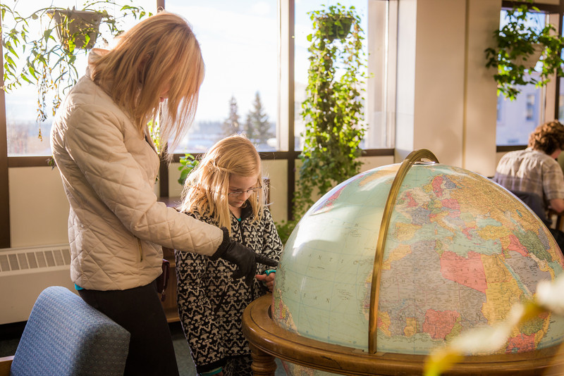 """Jaimee Coon points out some features on the globe while visiting the Rasmuson Library with her third grade daughter Amaya.  <div class=""""ss-paypal-button"""">Filename: LIF-14-4045-94.jpg</div><div class=""""ss-paypal-button-end"""" style=""""""""></div>"""