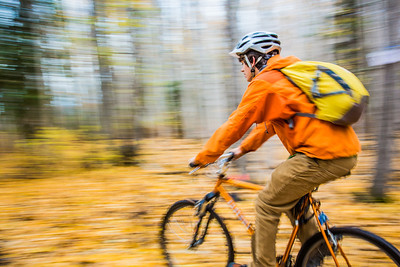 Mechanical engineering major Adam McCombs rides his bike through the woods towards campus on a recent foggy morning.  Filename: LIF-12-3556-145.jpg