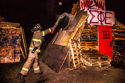 A student with the University Fire Department douses one of the bonefire structures with gasoline moments before they were torched during traditional Starvation Gulch activities Sept. 29.  Filename: LIF-12-3571-070.jpg