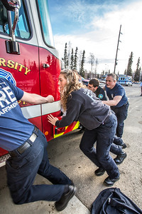 Crew members on shift at the University Fire Department's University Avenue station push the newest engine in the fleet into its place in the garage by hand.  Filename: LIF-14-4152-39.jpg
