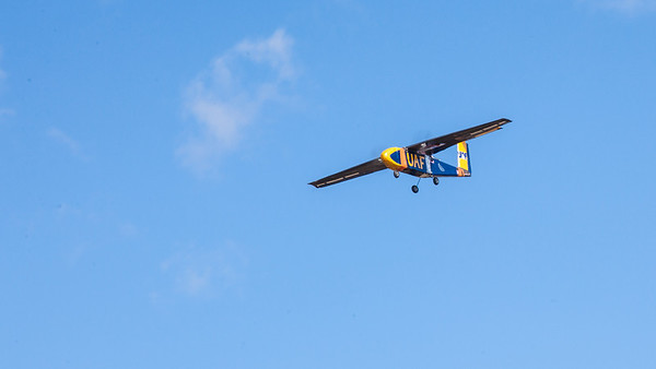 A model airplane built and designed by students in the UAF Aero Club soars over a parking lot on the Fairbanks campus during a successful test flight.  Filename: LIF-12-3366-071.jpg