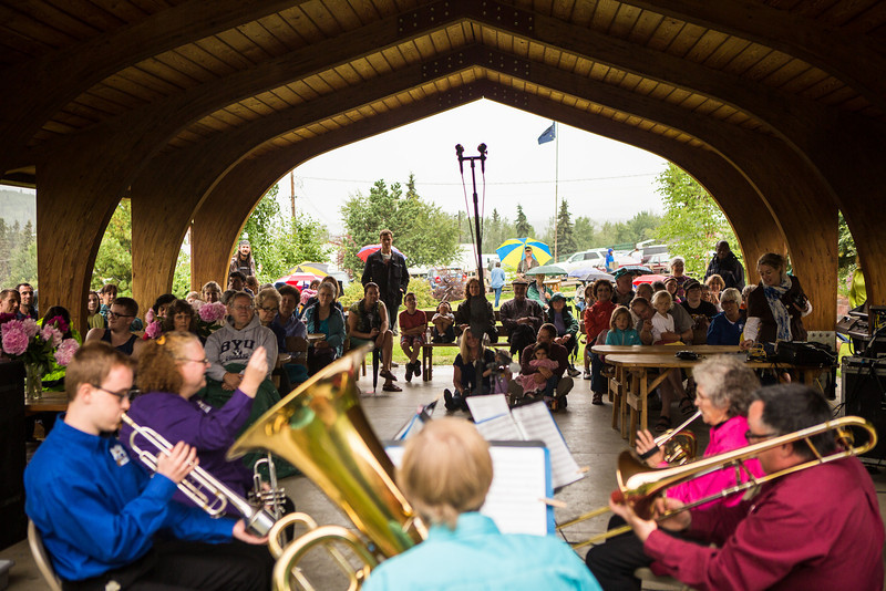 """People take shelter at the pavilion while a handful of individuals brave the weather with their umbrellas as they listen to music by the Opera Fairbanks Orchestra Brass on a rainy evening at the Georgeson Botanical Garden as part of Summer Sessions' Music in the Garden series.  <div class=""""ss-paypal-button"""">Filename: LIF-13-3884-14.jpg</div><div class=""""ss-paypal-button-end"""" style=""""""""></div>"""