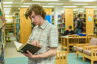 Freshman political science major Jake Gerrish looks through the stacks on the 5th floor of the Rasmuson Library.  Filename: LIF-14-4045-86.jpg