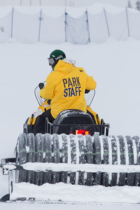 Student employees and staff members work to groom the big jump on UAF's Terrain Park on a snowy spring afternoon.  Filename: LIF-13-3721-66.jpg