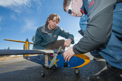 Engineering students Sam Brewer, left, and Corey Upton adjust their model plane before sending it aloft for a test flight over a parking lot on the Fairbanks campus.  Filename: LIF-12-3366-004.jpg
