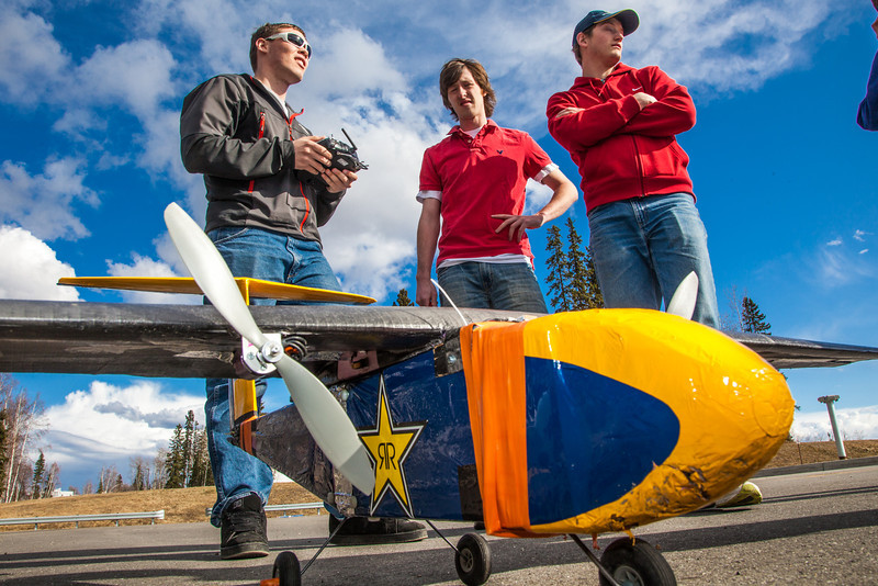 "Engineering student Corey Upton handles the remote controller while fellow team members Kyle Emery, center, and club president David Apperson stand by during a demonstration flight of their model airplane. The group designed and built the four-foot wingspan plane and competed in a national contest in April in Wichita, KS.  <div class=""ss-paypal-button"">Filename: LIF-12-3366-041.jpg</div><div class=""ss-paypal-button-end"" style=""""></div>"