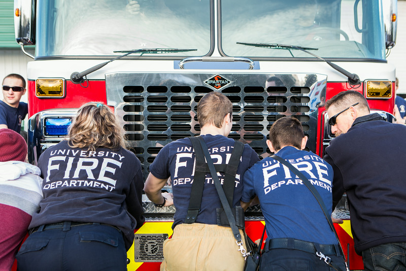 """University Firefighters push the newest fire engine, Ladder 11, into the garage.  <div class=""""ss-paypal-button"""">Filename: LIF-14-4153-27.jpg</div><div class=""""ss-paypal-button-end""""></div>"""