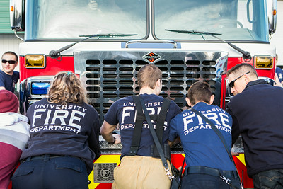 University Firefighters push the newest fire engine, Ladder 11, into the garage.  Filename: LIF-14-4153-27.jpg