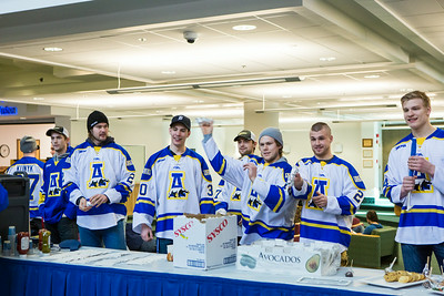 Hockey players toss hot dogs during the Keep the Cup Preparty rally at the Wood Center.  Filename: LIF-14-4103-24.jpg