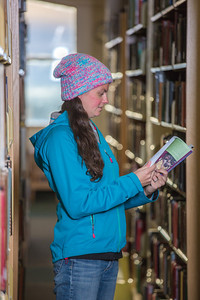Senior biology major Sarah Dewitt looks through the stacks on the 6th floor of the Rasmuson Library.  Filename: LIF-14-4045-133.jpg