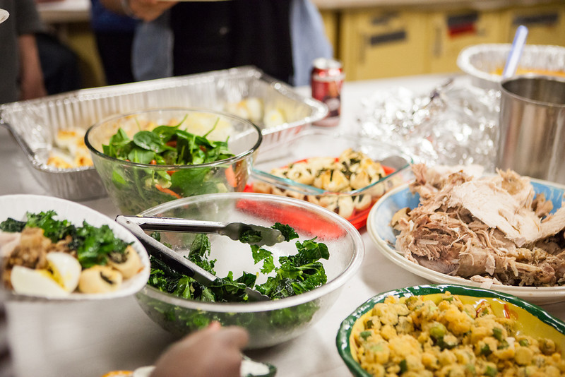 """The ceramic tables, which usually are a workstation for student potters working with clay is transformed to a table spread, filled with delicious food at the annual Thanksgiving gathering at the ceramics department.  <div class=""""ss-paypal-button"""">Filename: LIF-12-3660-59.jpg</div><div class=""""ss-paypal-button-end"""" style=""""""""></div>"""
