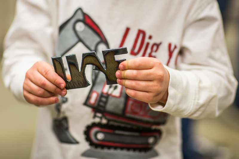 """Cooper Mitchell holds a UAF steel cutout during  the annual Eweek open house in the Duckering Building on campus.  <div class=""""ss-paypal-button"""">Filename: LIF-13-3741-119.jpg</div><div class=""""ss-paypal-button-end"""" style=""""""""></div>"""
