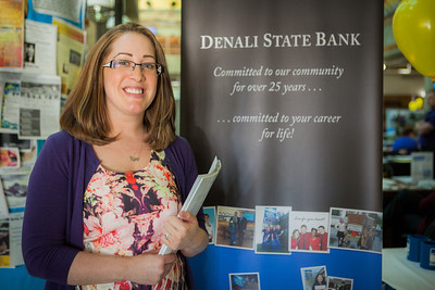 Alumna Betsy Campbell in Business Administration stands by the Denali State Bank booth at the Student Job and Internship Fair. Campbell is now currently the Branch Manager of Denali State Bank.  Filename: LIF-13-3745-74.jpg
