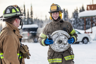 Spencer McLean, left, and Aaron Stevens roll up a couple of fire hoses after filling an outdoor ice rink for children at Ice Alaska's George Horner Ice Park in Feb. 2013.  Filename: LIF-12-3723-222.jpg
