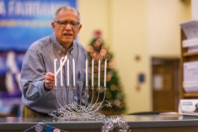 Professor Larry Kaplan lights a menorah on display in Signers' Hall on the third day of Hanukkah, 2014.  Filename: LIF-14-4417-13.jpg