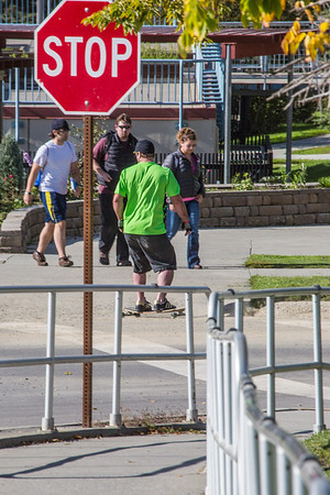 A skateboarder rides the sidewalk down the hill past the Commons on a beautiful September afternoon on the Fairbanks campus.  Filename: LIF-13-3934-1.jpg