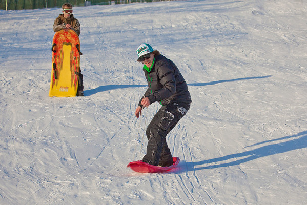 """Jimmy Donohue, surf-sledding, and his buddy Bryan Johnson spend some quality time on the UAF sledding hill on a nice February afternoon.  <div class=""""ss-paypal-button"""">Filename: LIF-12-3290-25.jpg</div><div class=""""ss-paypal-button-end"""" style=""""""""></div>"""