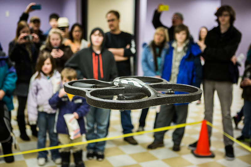 """Children and their parents watch a flight demonstration during the E-Week open house in the Duckering Building.  <div class=""""ss-paypal-button"""">Filename: LIF-13-3741-101.jpg</div><div class=""""ss-paypal-button-end"""" style=""""""""></div>"""