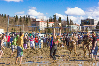 A participant in the 2014 SpringFest mud volleyball bouts sets up a teammate.  Filename: LIF-14-4167-78.jpg