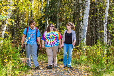 Demetri Martin-Urban, left, Grace Amundsen, center, and Kaylie Wiltersen stroll through the woods near the west entrance to campus on a nice fall afternoon.  Filename: LIF-12-3544-145.jpg