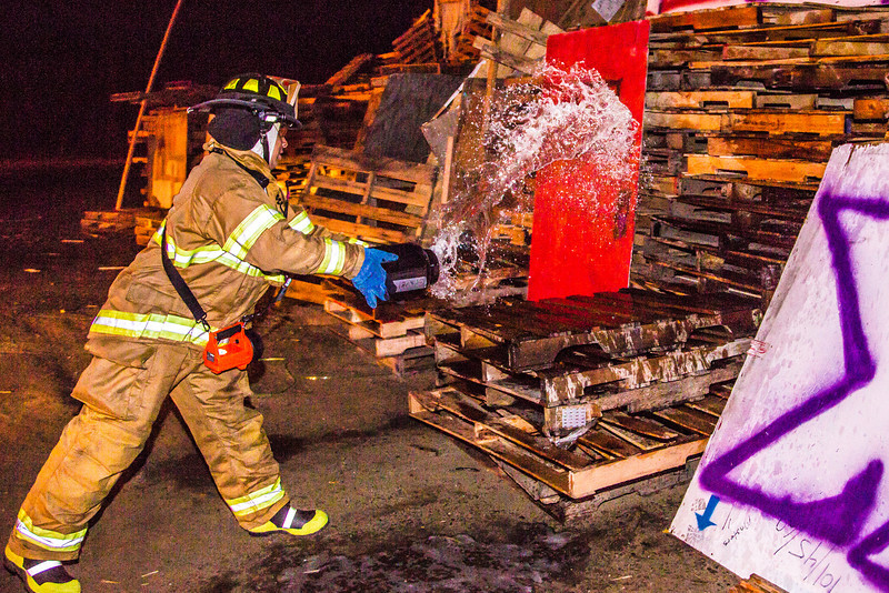 """A student with the University Fire Department douses one of the bonefire structures with gasoline moments before they were torched during traditional Starvation Gulch activities Sept. 29.  <div class=""""ss-paypal-button"""">Filename: LIF-12-3571-068.jpg</div><div class=""""ss-paypal-button-end"""" style=""""""""></div>"""
