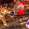 "A student with the University Fire Department douses one of the bonefire structures with gasoline moments before they were torched during traditional Starvation Gulch activities Sept. 29.  <div class=""ss-paypal-button"">Filename: LIF-12-3571-068.jpg</div><div class=""ss-paypal-button-end"" style=""""></div>"