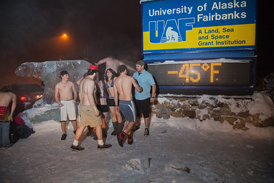 A group of hardy UAF students get ready to join the 40°below club by posing in their shorts or swimsuits by the time & temperature sign at an extreme temperature of 40° below or colder.  Filename: LIF-12-3269-17.jpg
