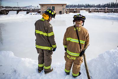 Aaron Stevens, left, and Spencer McLean fill an outdoor ice rink for children at Ice Alaska's George Horner Ice Park in Feb. 2013.  Filename: LIF-12-3723-97.jpg