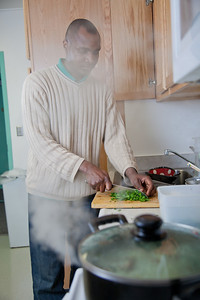 Peter Ikewun, a petroleum engineeering graduate student from Nigeria, prepares a traditional African soup in his communal Wickersham Hall kitchen.  Filename: LIF-12-3268-060.jpg