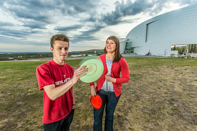 Friends Aaron Druyvestein and Serena McCormick enjoy a round of disc golf on the campus course near the University of Alaska Museum of the North.  Filename: LIF-14-4191-80.jpg