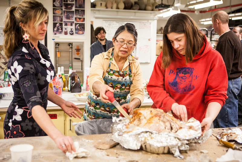"""From left, Danielle Anderson, Mary Blurton, and Teresa Shannon carve a turkey before the feasting begins at the annual Thanksgiving gathering at the ceramics department.  <div class=""""ss-paypal-button"""">Filename: LIF-12-3660-34.jpg</div><div class=""""ss-paypal-button-end"""" style=""""""""></div>"""