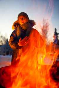 With temperatures near 35 below zero, Celia Miller warms her hands by the fire during the Honors Program week-long vigil in Constitution Park to draw attention to the plight of the homeless.  Filename: LIF-11-3224-04.jpg