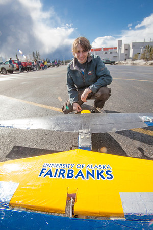 Engineering major Sam Brewer poses with a model plane he helped build and design before sending it aloft for a test flight over a parking lot on the Fairbanks campus.  Filename: LIF-12-3366-013.jpg