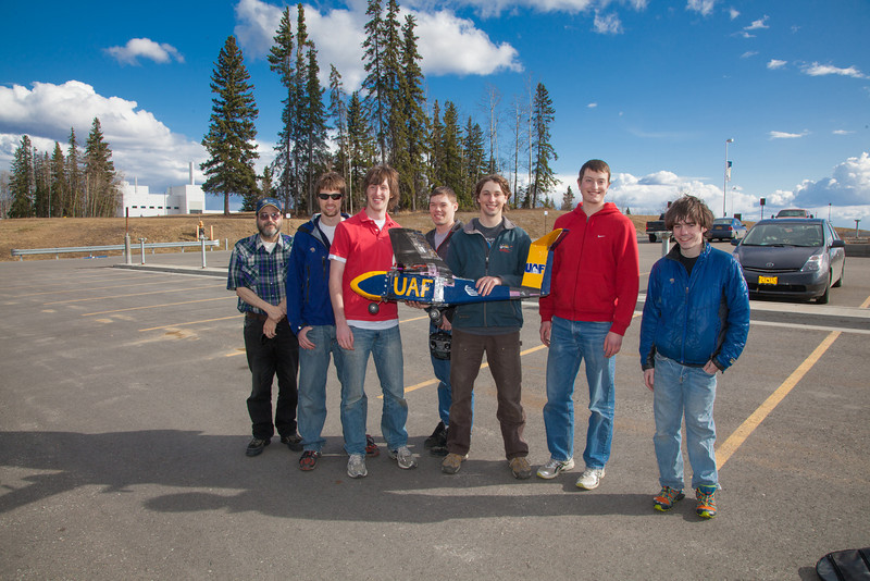 """Engineering majors in the UAF Aero Club gather with their model plane after sending it aloft for a test flight over a parking lot on the Fairbanks campus.  <div class=""""ss-paypal-button"""">Filename: LIF-12-3366-100.jpg</div><div class=""""ss-paypal-button-end"""" style=""""""""></div>"""