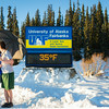 "Sporting shorts and a t-shirt in above freezing temperatures in January, Megan Lasselle and Seth Reddell kiss in front of the time and temperature sign.  <div class=""ss-paypal-button"">Filename: LIF-14-4047-49.jpg</div><div class=""ss-paypal-button-end""></div>"