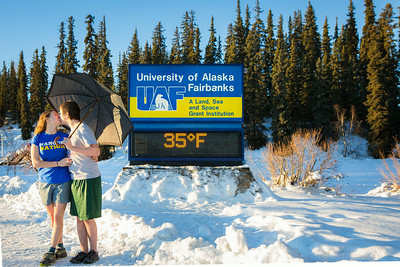 Sporting shorts and a t-shirt in above freezing temperatures in January, Megan Lasselle and Seth Reddell kiss in front of the time and temperature sign.  Filename: LIF-14-4047-49.jpg
