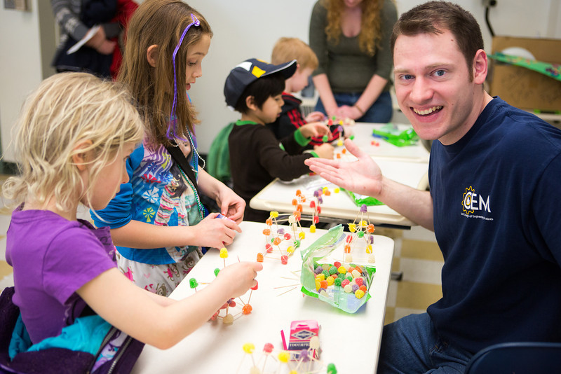 """Engineering student Andrew Chamberlain helps out young engineers build their gumdrop bridges during the during the E-Week open house in the Duckering Building.  <div class=""""ss-paypal-button"""">Filename: LIF-13-3741-54.jpg</div><div class=""""ss-paypal-button-end"""" style=""""""""></div>"""