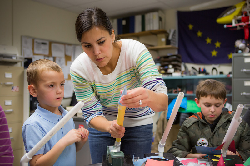 """Charlotte LaRue helps son Braun Endicott with his paper rocket during the E-Week open house in the Duckering Building.  <div class=""""ss-paypal-button"""">Filename: LIF-13-3741-14.jpg</div><div class=""""ss-paypal-button-end"""" style=""""""""></div>"""
