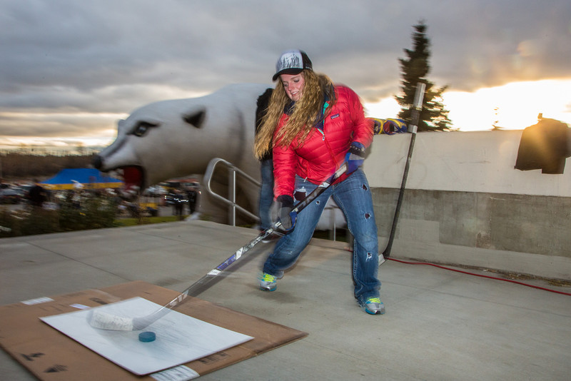 "Tori Middelstadt tries her hand at a slap shot during festivities surrounding the Starvation Gulch celebration in front of the Patty Center.  <div class=""ss-paypal-button"">Filename: LIF-12-3570-049.jpg</div><div class=""ss-paypal-button-end"" style=""""></div>"