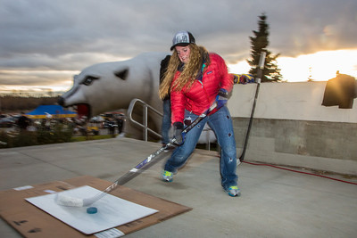 Tori Middelstadt tries her hand at a slap shot during festivities surrounding the Starvation Gulch celebration in front of the Patty Center.  Filename: LIF-12-3570-049.jpg