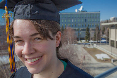 Senior foreign languages major Lindsey Miller poses in her cap and gown on the roof of the Brooks Building on the Fairbanks campus.  Filename: LIF-12-3352-91.jpg