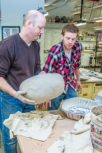 Professor Jim Brashear, left, lifts a turkey into a roasting pan with assistance from art major Ian Wilkinson in the UAF Fine Arts complex. The unique cooking process has been perfected over the past 20 years by Brashear who hosts a feast each year for hungry students on campus over Thanksgiving break.  Filename: LIF-12-3659-93.jpg