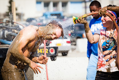Fabienne Clerc hoses off Michael Weingartner after a game of mud volleyball during the 2012 Spring Fest tournament.  Filename: LIF-12-3378-37.jpg