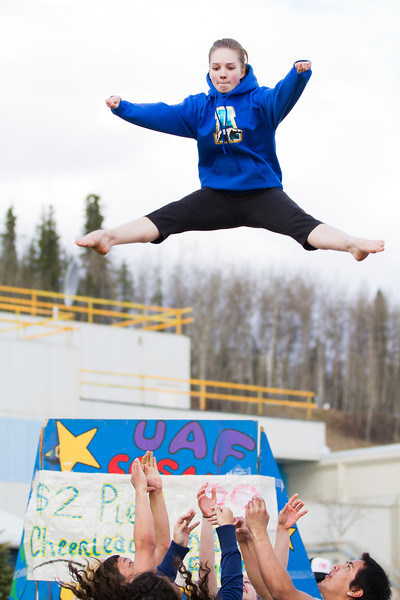 """Lindsey Dudley demonstrates a routine in front of a UAF Cheerleading fundraiser stand at the 2012 Spring Fest field day activities.  <div class=""""ss-paypal-button"""">Filename: LIF-12-3384-231.jpg</div><div class=""""ss-paypal-button-end"""" style=""""""""></div>"""