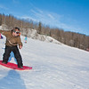 """Bryan Johnson surfs down the SRC sledding Hill on a sunny day in February.  <div class=""""ss-paypal-button"""">Filename: LIF-12-3289-92.jpg</div><div class=""""ss-paypal-button-end"""" style=""""""""></div>"""