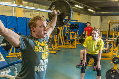 Gavin Meggert pumps some iron during a workout in the Student Recreation Center under the guidance of a student trainer.  Filename: LIF-14-4111-77.jpg